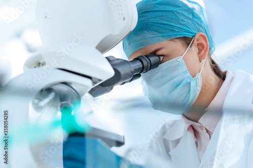 female scientist looking carefully through a microscope. Wallpaper Mural