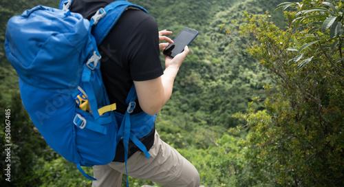 Cuadros en Lienzo Woman hiker using smartphone on forest mountain top