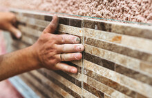 Master Tiler Glues  Wall  Tiles. Concept Of The  Contruction.