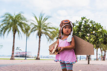 Happy Asian Funny Child Or Kid Little Girl Smile Wear Pilot Hat And Goggles Play Toy Cardboard Airplane Wing Flying Against Summer Sky Cloud On Trees Garden Background, Startup Freedom Concept