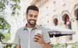 Young handsome student man using smartphone. Smiling joyful guy summer portrait. Cheerful men holding mobile phone