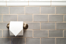 Roll Of Toilet Paper On Brass Holder Against A Gray Tile Wall