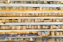 A Large Pile Of Boards Sawn From Trees On A Sawmill For The Procurement Of Building Materials For Construction. Construction Industry.