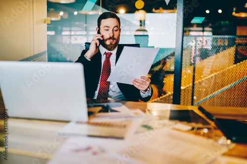 Foto Bearded experienced entrepreneur in formal wear reading financial reports and calling to manager on smartphone to discuss data