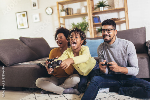 Fotografia, Obraz African American family at home sitting in sofa couch and playing console video