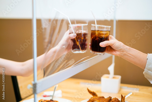 Fototapeta Asian beautiful female clinking a glass of water with her mother who siting sepa