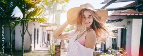 Obraz na plátně Beautiful happy blonde girl in a straw hat smiles joyfully, summer travel in the tropics