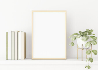 Poster mockup with vertical gold metal frame on the table with green plant in pot, books and trendy interior decoration on empty white wall background. A4, A3 size format. 3D rendering, illustration.
