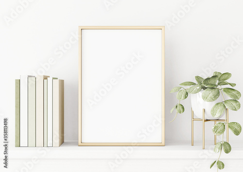 Fotomural Poster mockup with vertical gold metal frame on the table with green plant in pot, books and trendy interior decoration on empty white wall background
