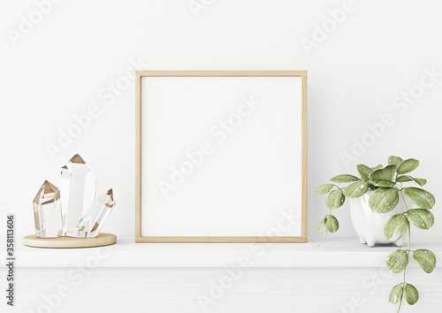 Obraz na plátně Interior poster mockup with square wooden frame on the shelf with green plant in pot, crystals and trendy decoration on empty white wall background