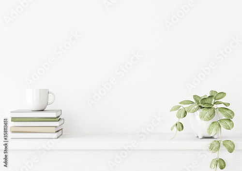 Fotografía Interior wall mockup with green plant in pot and pile of books with cup on empty white background with free space on center