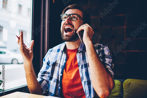 Photo Casual dressed angry bearded young man crying and arguing during phone conversation on smartphone device