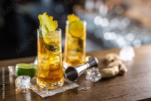 Fotografia Two glasses of ginger bourbon cocktail with ice cubes and fresh ginger on a wood