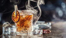 Smoked Old Fashioned Rum Cocktail With Cubes Of Ice Around On A Dark Background