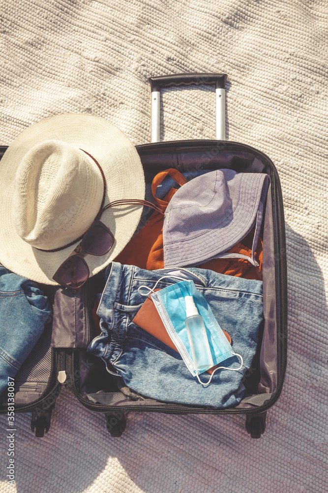 Fototapeta Travel.Todler sits near a suitcase with things and dreams of a vacation traveling after quarantine, lockdown, covid 19. Staycation.local travel.Tourism after the opening of borders, end of quarantine