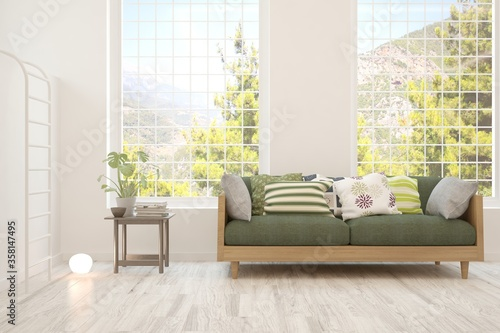 Photo White living room with sofa and summer landscape in window