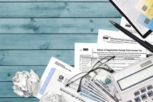 IRS Form 990 Return Of Organization Exempt From Income Tax Lies On Flat Lay Office Table And Ready To Fill. U.S. Internal Revenue Services Paperwork Concept. Time To Pay Taxes
