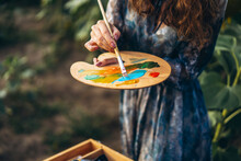 Close Up Hands Of Female Artist Holding Brush And Palette With Oil Paints. Blurred Background With Easel In Sunflower Field