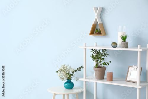 Fototapeta Stylish rack with decor near color wall obraz