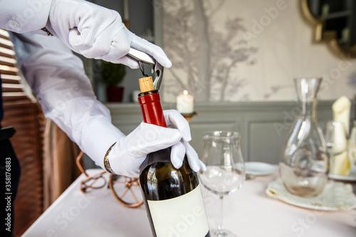 Fototapeta Sommelier opening wine bottle