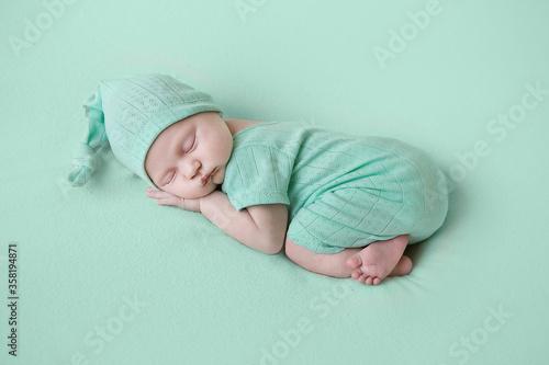 Fototapeta beautiful newborn girl in a mint suit sleeps on a mint background