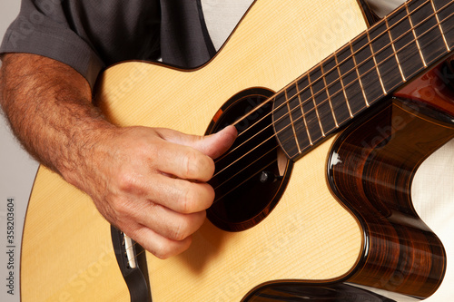 close up of man playing a guitar by picking the strings Tablou Canvas
