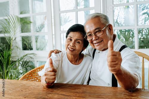Fototapeta Cheerful Asian man and woman hugging each other and showing thumb up gesture while sitting at table in cozy room at home obraz