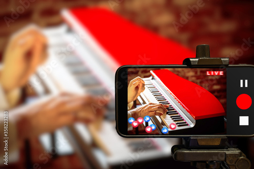 Fototapeta music vlogger streaming a live video while playing piano at home obraz