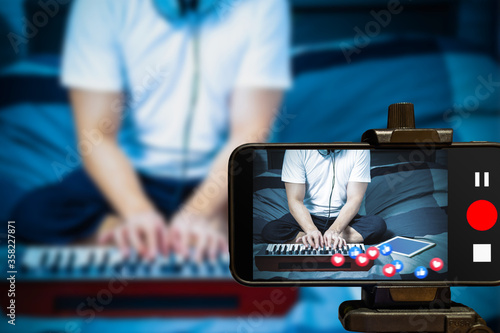 music vlogger streaming a live video while playing keyboard synthesizer at home Fototapeta