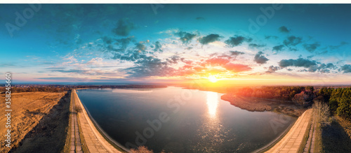 Obraz Sunrise over lake in early spring. Serene lake in the morning. Nature landscape. Dam on the lake. View from above. Panorama - fototapety do salonu