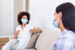 Two female best friends sitting in social distance wearing face mask and talking on the sofa, preventing covid 19 coronavirus infection spread.