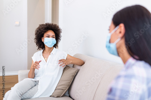 Canvastavla Two female best friends sitting in social distance wearing face mask and talking on the sofa, preventing covid 19 coronavirus infection spread