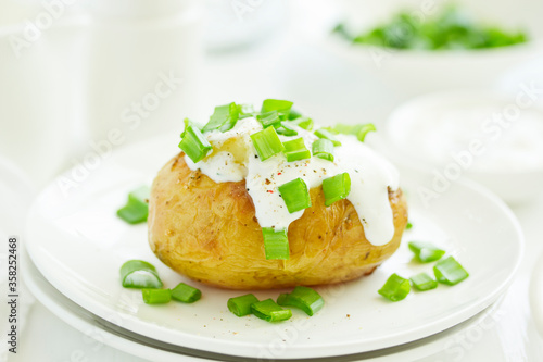 Fototapeta Baked potatoes with cheese, served with sour cream and onions. Selective focus obraz