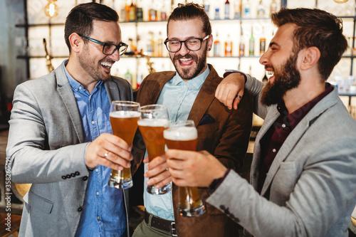 Obraz na plátně Happy young businessmen drinking beer and talking at pub after work