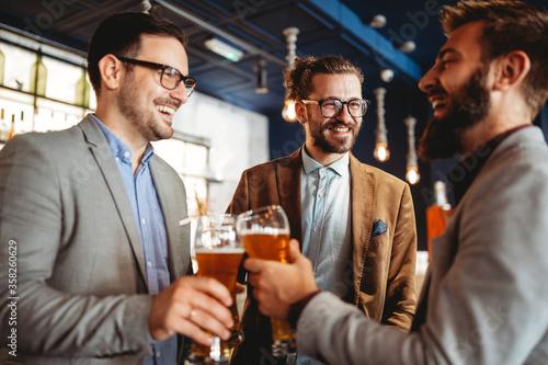 Obraz Business people drink beer after work in pub. Businessmen enjoy a beer. - fototapety do salonu