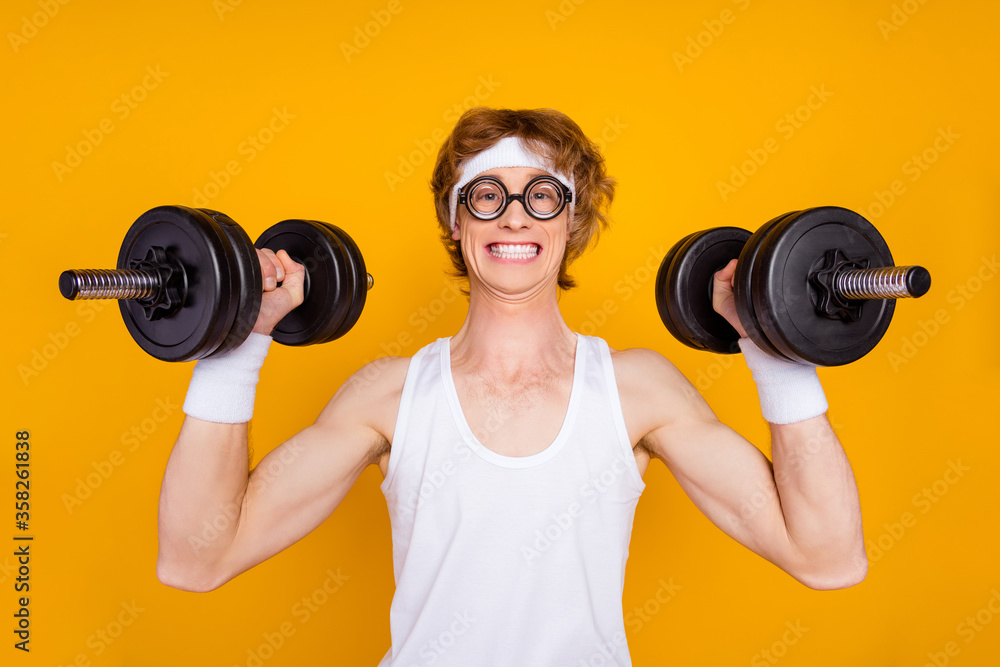 Fototapeta Close-up portrait of his he nice attractive funky cheerful cheery motivated guy sportsman lifting barbell doing good work out isolated over bright vivid shine vibrant yellow color background