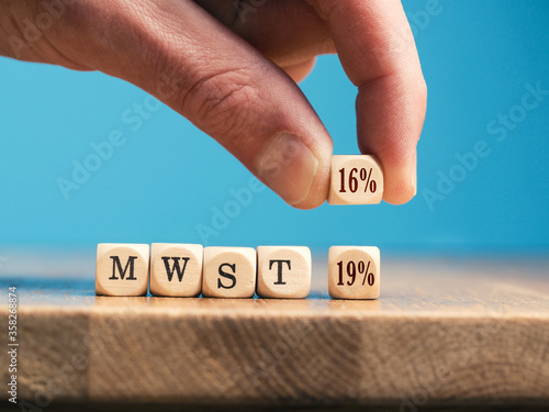 A businessman exchanges a wooden cube with 19% tax for one with 16% tax. Economic stimulus package for Germany concept.