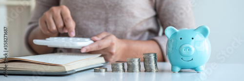 Photo Young woman and piggy bank to planning growing saving strategy with pile coins