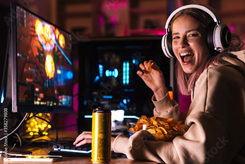 Fotografie, Tablou Image of excited cute girl eating chips while playing video game