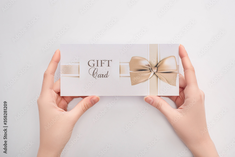 Fototapeta Top view of woman holding gift card in hands on white background