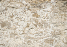 Close Up Of A Crumbling Old Clunch (soft Limestone) Wall With Flaking Lime Wash.