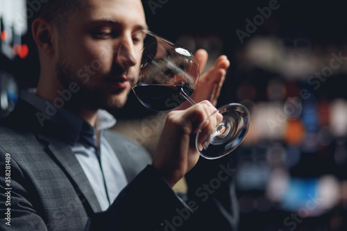 Fototapeta Connoisseur wine sommelier feels aroma and taste in restaurant obraz