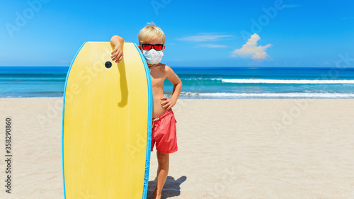 Fototapeta Young surfer wearing sunglasses, protective mask on sea beach with body board. Summer tours, cruises cancellation due to coronavirus COVID-19 epidemic. Safe travel destinations for family vacation. obraz