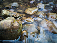 Stones Protrude From The Water In A Small Hilly Stream.