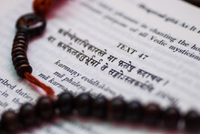 A Text From Hindu Sacred Book Bhagavad Gita Along With Rosary.