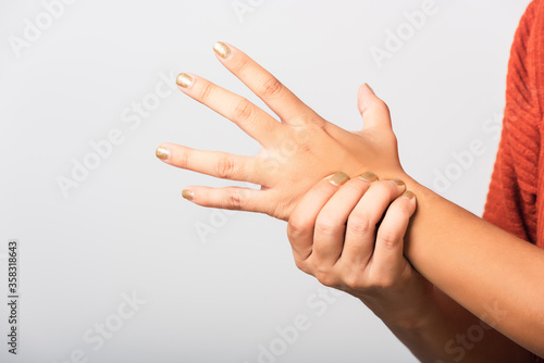 Photo Close up hand of Asian woman she holding her acute pain in wrist of hands, studi