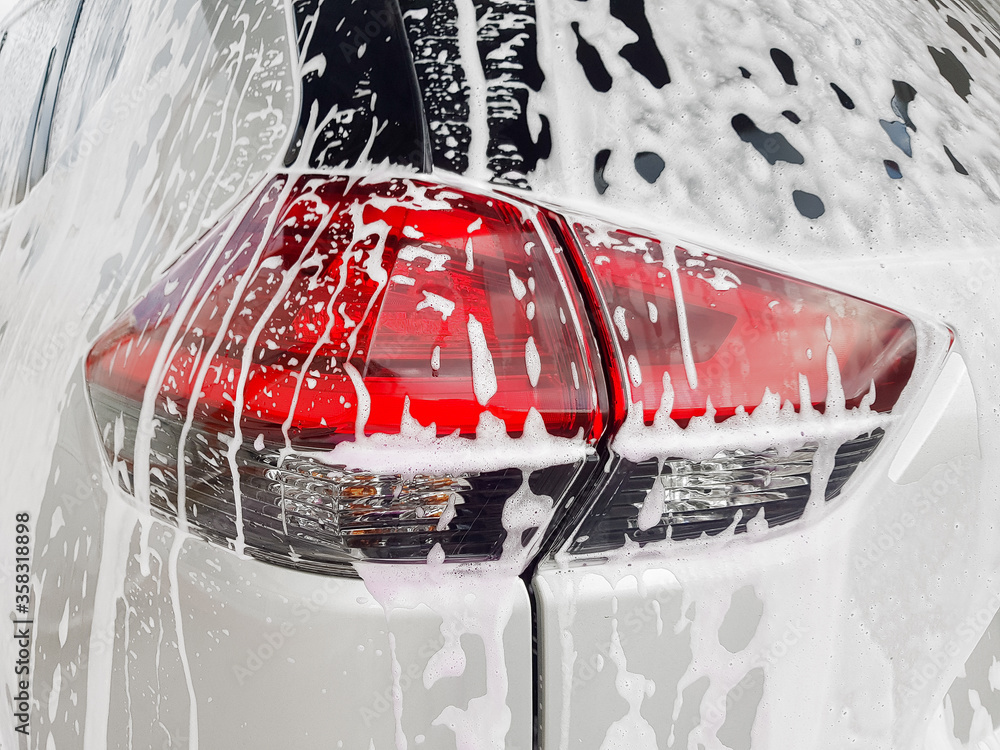 Fototapeta car taillight on back lid covered with active foam for washing a dirty car and  wax, close up of the process of detailing vehicle care.