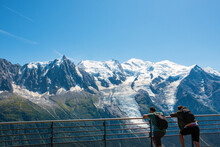 Two Friends (unidentified People, Back View) Admiring Beautiful Snow Covered Mont Blanc Mountains Range And Aiguille Du Midi From Planpraz. Alps Summer Travel. France Nature Hiking Tourism Background.