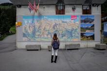 Jun 2016, Zermatt, Switzerland. A Woman Tourist Looking At A Big Tourist Information On The Wall.
