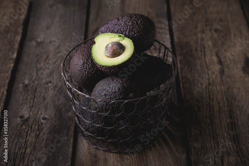 Fototapeta Hass avocado in a basket on a wooden table